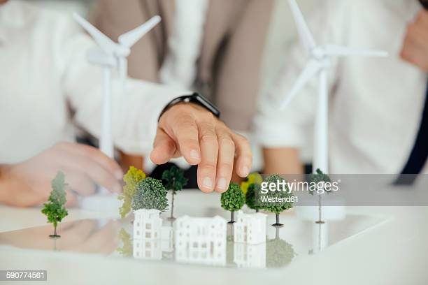 close-up of business people wind turbine model and houses on conference table - environmental conservation stock photos and pictures