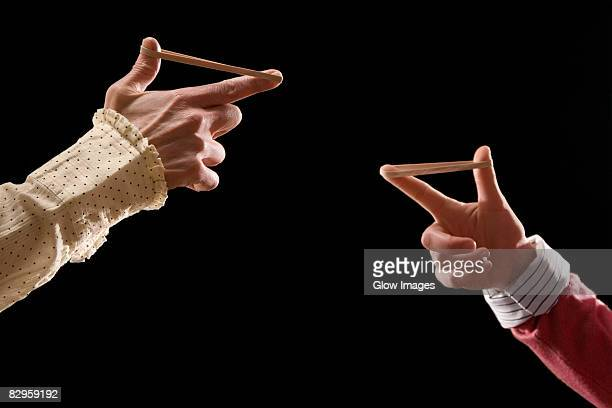 Close-up of business people's fingers stretching rubber bands