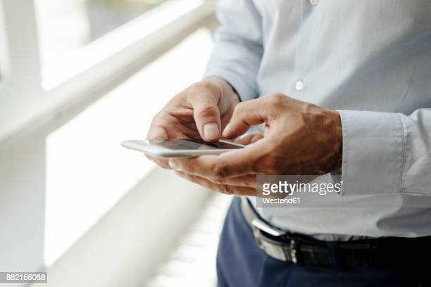 close-up of businessman at the window using cell phone - sms'en stockfoto's en -beelden
