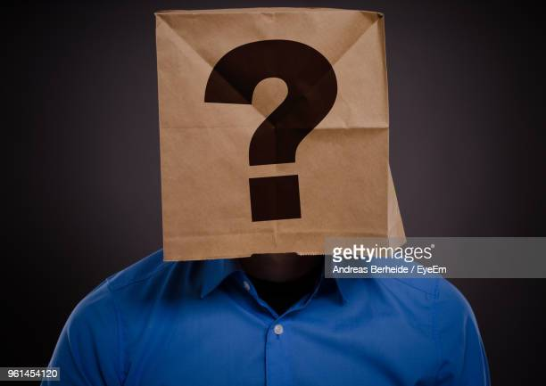 Close-Up Of Businessman Carrying Paper Bag With Question Mark On Head Standing Against Black Background