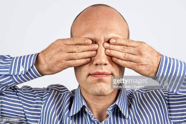 close-up of businessman covering eyes with hands against white background - hands covering eyes stock pictures, royalty-free photos & images