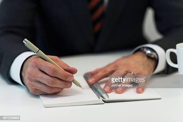 Close-up of businessman doing notes, Stockholm, Sweden