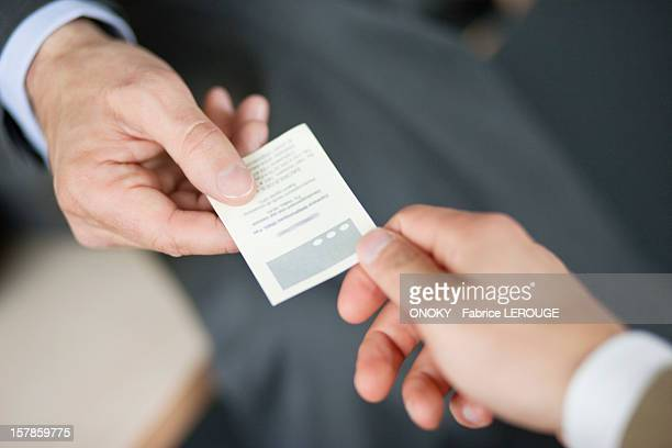 Close-up of Businessman giving card to another businessman