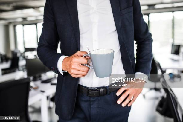 Close-up of businessman holding coffee mug in office
