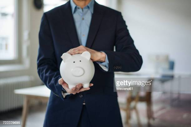 close-up of businessman holding piggy bank - gier stock-fotos und bilder