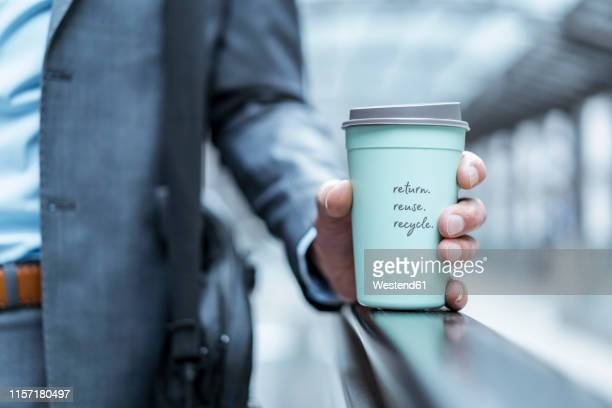 close-up of businessman holding recycable takeaway coffee cup - kaffee getränk stock-fotos und bilder