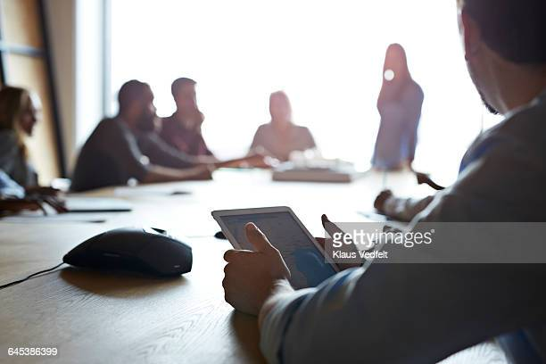 Close-up of businessman holding tablet at meeting
