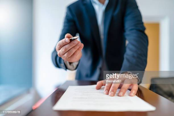 close-up of businessman in office presenting ballpen and contract - request stock pictures, royalty-free photos & images