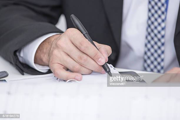 Close-up of businessman in office writing in organizer