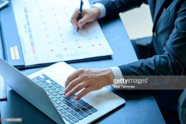 close-up of businessman making a notes schedule meeting at calendar during work. - month stock pictures, royalty-free photos & images