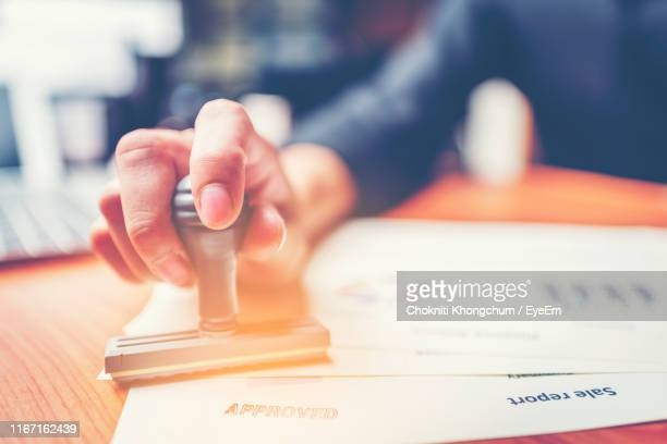 close-up of businessman putting approved stamp on document in office - permission concept stock pictures, royalty-free photos & images