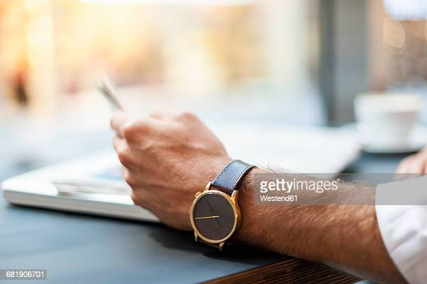 close-up of businessman reading newspaper in a cafe - watch timepiece stock pictures, royalty-free photos & images