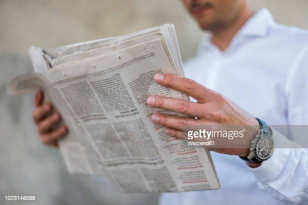 close-up of businessman reading newspaper - de media stockfoto's en -beelden