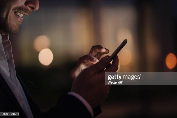 close-up of businessman text messaging - images stock-fotos und bilder