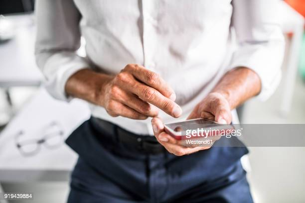 close-up of businessman using cell phone in office - rolled up sleeves fotografías e imágenes de stock