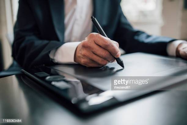 close-up of businessman using graphics tablet at desk in office - design professional stock pictures, royalty-free photos & images
