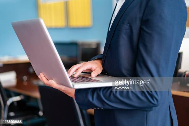 close-up of businessman using laptop in office - human body part stock pictures, royalty-free photos & images