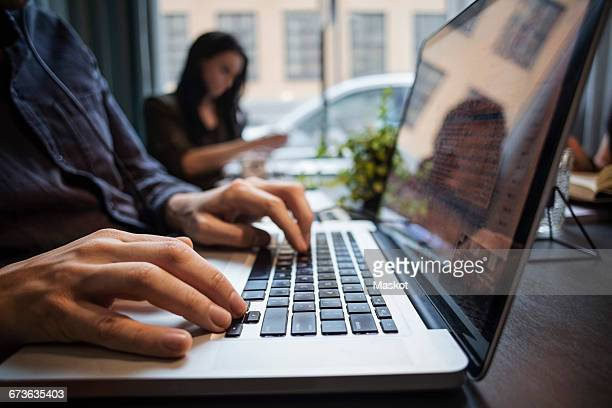 Close-up of businessman using laptop with colleague sitting at table in office