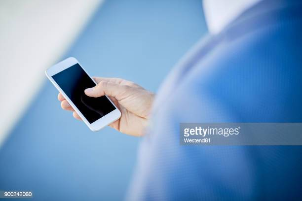 Close-up of businessman using smartphone outdoors in the city