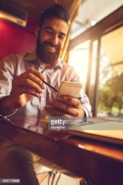 Close-up of businessman using stylus on smart phone.