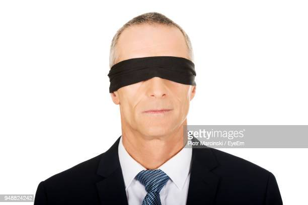 close-up of businessman with blindfold on eyes against white background - blindfolded stock photos and pictures