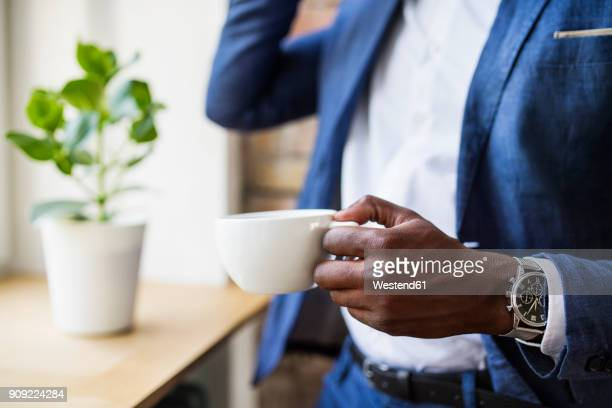 close-up of businessman with cup of coffee at the window - wrist watch stock pictures, royalty-free photos & images