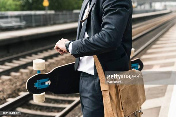 close-up of businessman with skateboard waiting at the platform - pendler stock-fotos und bilder