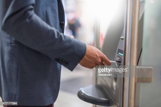 close-up of businessman withdrawing money at an atm - bankieren stock pictures, royalty-free photos & images