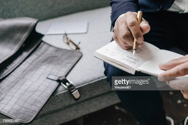 close-up of businessman writing and drawing in notebook - stift stock-fotos und bilder