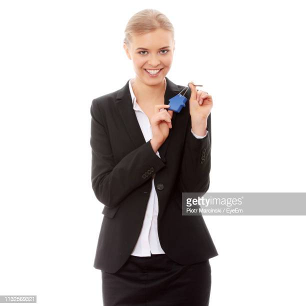 close-up of businesswoman holding key ring against white background - 膝から上の構図 ストックフォトと画像