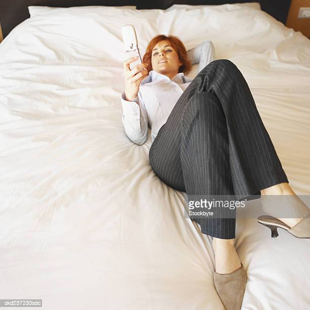 Close-up of businesswoman lying on bed holding mobile phone