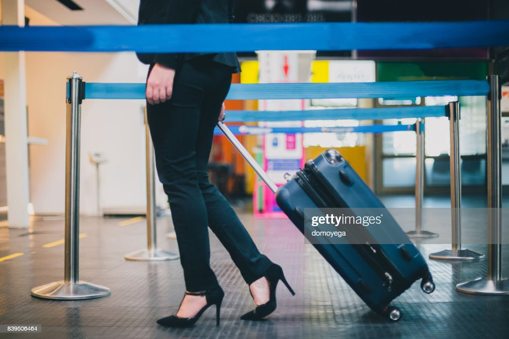 Close-up of businesswoman pulling suitcase to the check-in desk : Stock Photo