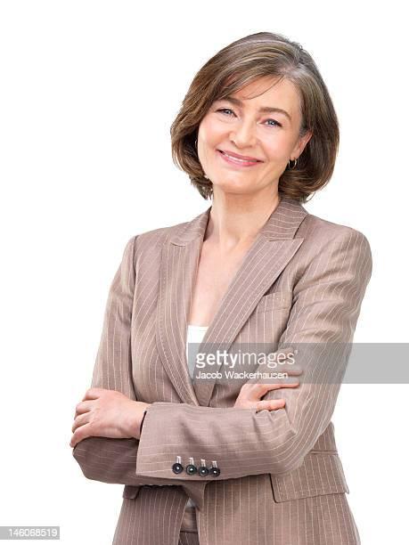 Gros plan de femme d'affaires souriant avec bras croisés contre fond blanc