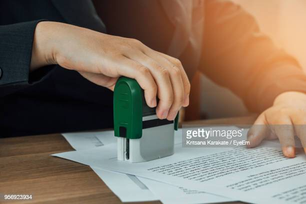 Close-Up Of Businesswoman Stamping Contract On Table