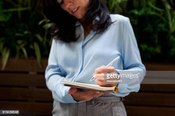 close-up of businesswoman taking notes - linkshandig stockfoto's en -beelden