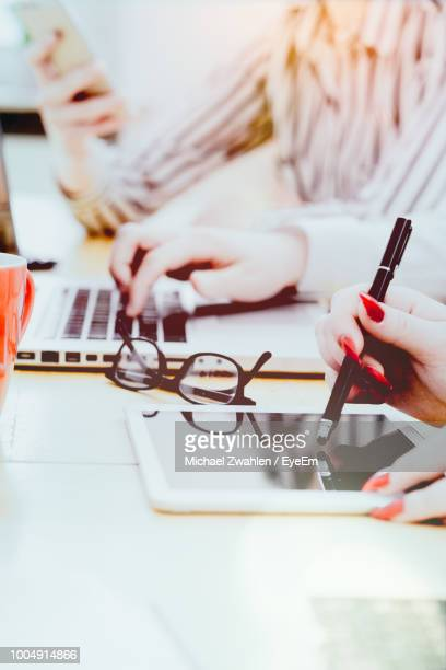 Close-Up Of Businesswoman Using Digitalized Pen On Digital Tablet While Working At Desk In Office