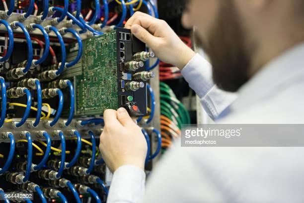 Nahaufnahme von beschäftigt Techniker installieren Festplatte im Server-Rack Schrank zur Verbesserung der Geschwindigkeit der Supercomputer auf Bergbau farm