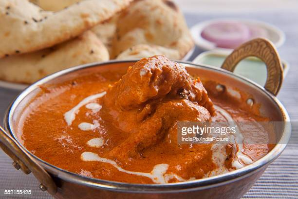 Close-up of butter chicken with tandoori rotis