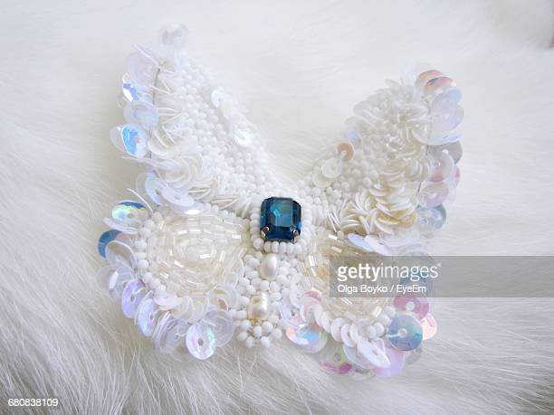 Close-up Of Butterfly Shape Jewelry On White Fur