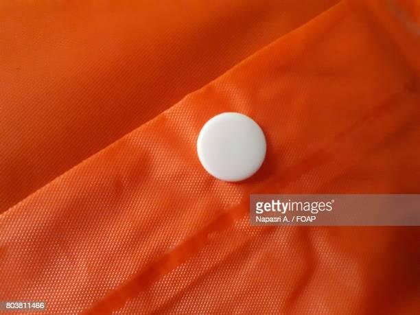 Close-up of button on orange raincoat