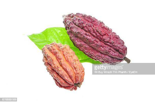 Close-Up Of Cacao Fruits And Leaf Against White Background
