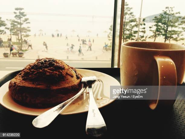 Close-Up Of Cake In Plate By Coffee Cup On Table