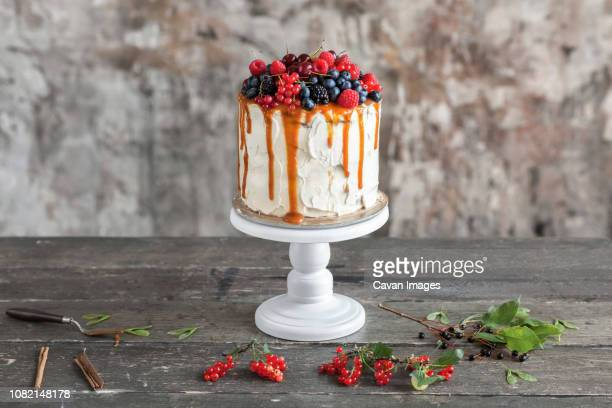 close-up of cake with caramel and berry fruits on wooden table against rusty wall at home - cakestand stock pictures, royalty-free photos & images