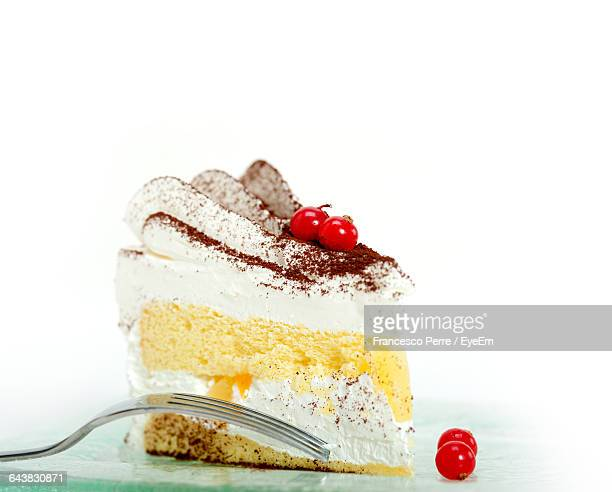 Close-Up Of Cake With Fork Against White Background