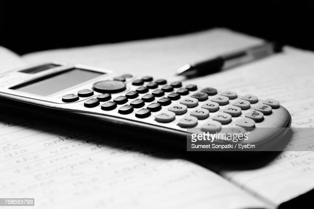 Close-Up Of Calculator And Book On Table