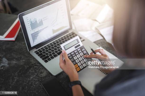 close-up of calculator and coins and asia young wonman analyzing financial data. accounting and financial concept. - rechnungswesen stock-fotos und bilder
