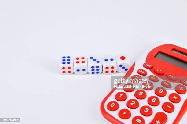 Close-Up Of Calculator With Dice Over White Background