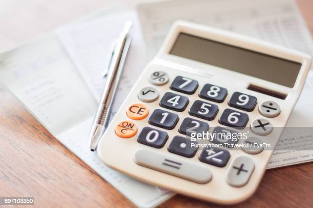 Close-Up Of Calculator With Pen And Passbook On Table