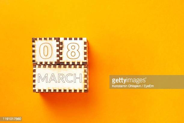 close-up of calendar date against orange background - internationale vrouwendag stockfoto's en -beelden