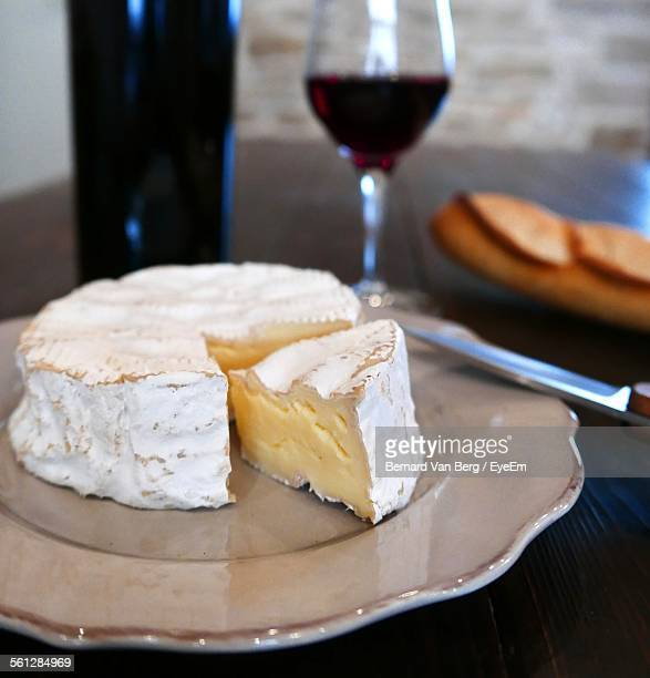 Close-Up Of Camembert With Baguette And Wine On Wooden Table
